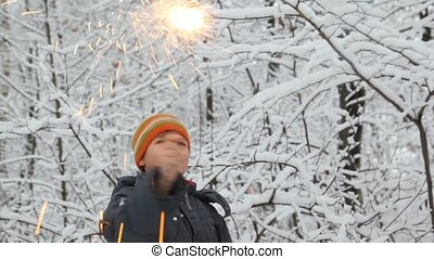 boy plays with sparkler waves it in winter forest