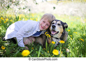 Happy Little Boy Relaxing in Flower Meadow and Hugging his Pet Dog