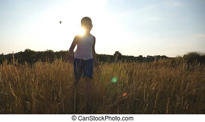 Happy little boy running at field behind camera with sun flare at background. Smiling male kid having fun in nature on a summer meadow. Child jogging outdoor at sunny day. Slow motion Close up