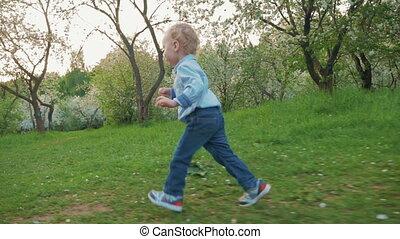 Happy little boy running in bloomy park