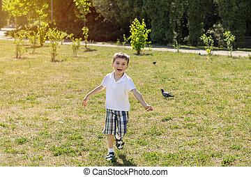 Happy little boy running on a lawn in the city park on a summer sunny day. Close up. Beautiful summer background with copy space