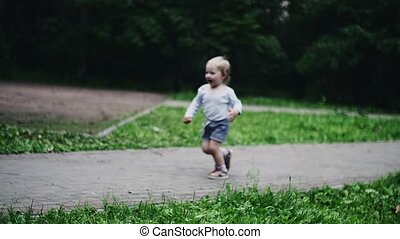 Happy little boy running on playground in summer park. Flying doves. Mother