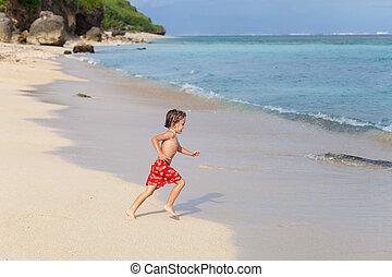 Happy little boy running on the beach
