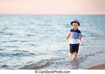 little boy running on the sea beach