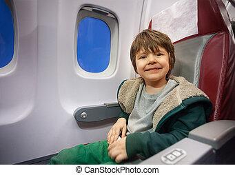 Happy little boy sit in commercial jet plane seat
