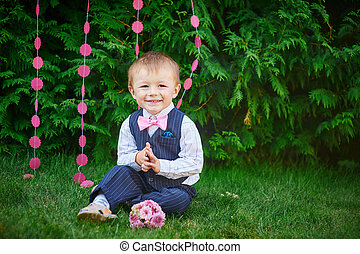 happy little boy sitting in the park on the grass