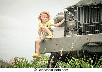 happy little boy sitting on the car