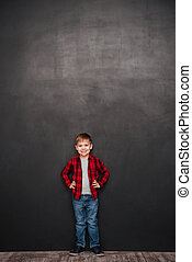 Happy little boy standing over chalkboard