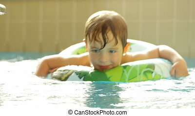 Happy little boy swimming with rubber ring in the pool