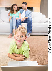 Happy little boy using laptop on the rug with parents sitting sofa at home in living room
