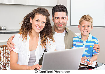 Happy little boy using laptop with parents at table at home...