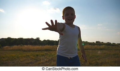 Happy little boy with an outstretched hand running at field behind camera and trying to catch it. Smiling male kid having fun in nature on a summer meadow. Child jogging outdoor. Slow motion