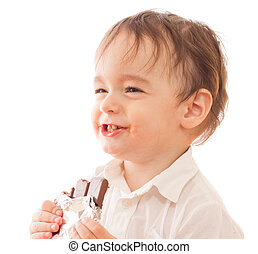 Happy little boy with bar of chocolate in his hands