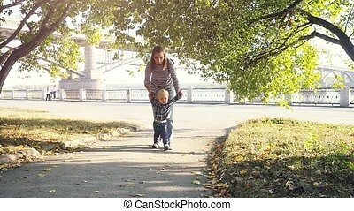 Happy little boy with his mother holding hands running along the road in the park in slowmotion in autumn. 1920x1080