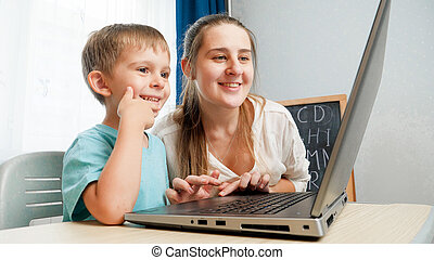 Happy little boy with mother smiling and looking on laptop screen. Amazed child using laptop computer