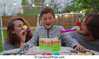 Happy little boy with parents blowing birthday candles. Parents dip a child face in a cake.