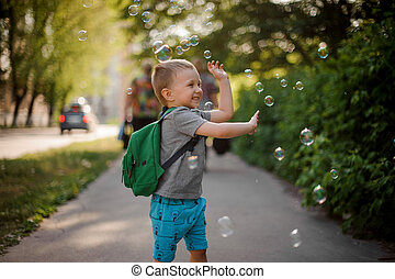 Happy little boy with soap bubbles in summer park on sunny day