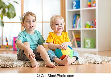 Happy little boys friends sitting on floor in kindergarten