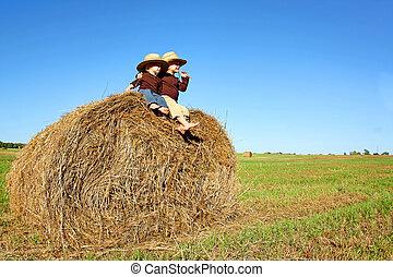 Happy Little Boys on Farm Sitting on Hay Bale