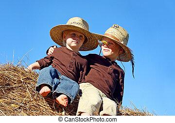 Happy Little Boys Sitting on Hay Bale