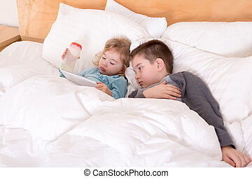 Happy little brother and sister lying in bed