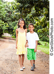 little brother and sister walking outdoors