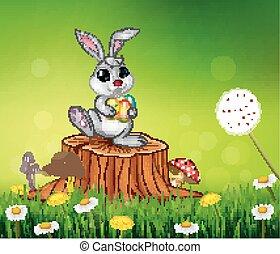 Happy little bunny holding egg