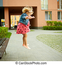 Happy little child, blonde toddler girl jumping