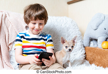 Happy little child boy playing online game, watching video on cellphone. Smiling small kid using funny mobile apps, enjoying free leisure time at home, play together with puppy dog chihuahua.