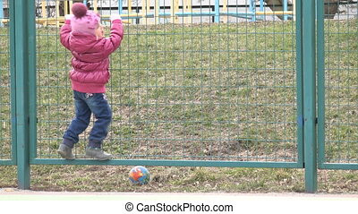 Happy Little Child, Girl  Having fun on the Playground Jumping on the Net