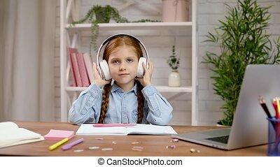 happy little child girl is listening to music on headphones.