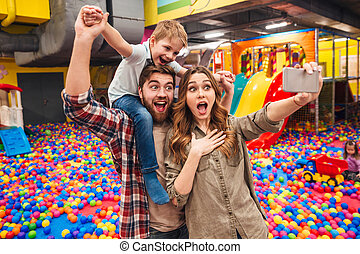 Happy little child have fun with his parents make selfie