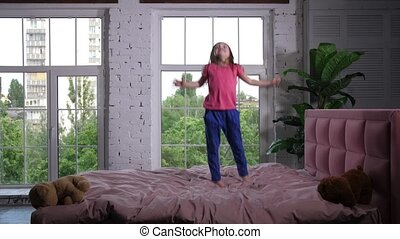 Happy little child jumping on cozy bed in bedroom - Adorable...
