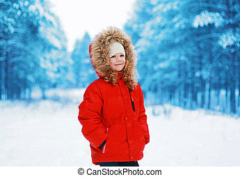 Happy little child outdoors in winter forest