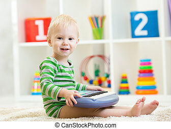 Happy little child playing piano toy