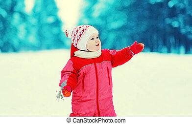 Happy little child walking in winter snowy forest