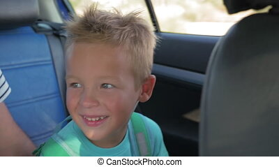 Happy little child with backpack traveling by car