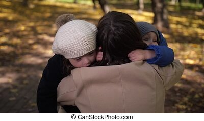 Happy little children cuddling with mother in park