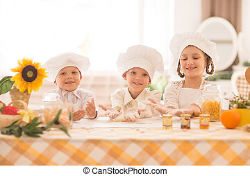 happy little children in the form of a chef to cook a delicious breakfast in the kitchen