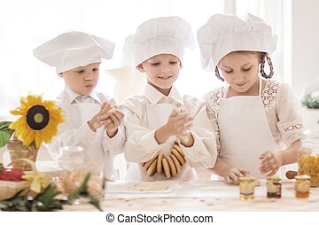 Happy little children in the shape of a chef to prepare delicious dishes