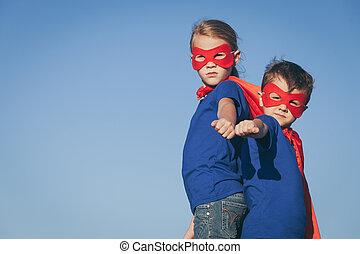 Happy little children playing superhero.