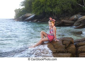Happy little cute girl at the beach