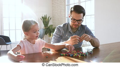 Smiling dad entertaining enjoying hobby time with adorable small daughter.