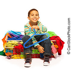 Happy little dark skinned boy want more clothes even sitting...