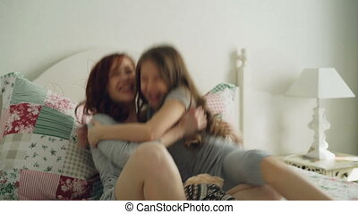 Happy little daughter emabracing her young cheerful mother sitting on bed in bright bedroom at home