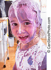 Happy little future artist covered in paint