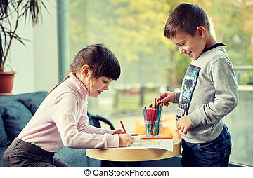 happy little girl and boy drawing at home