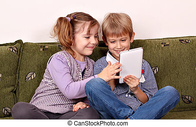 happy little girl and boy playing with tablet pc