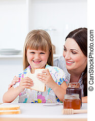 Happy little girl and her mother eating slices of bread