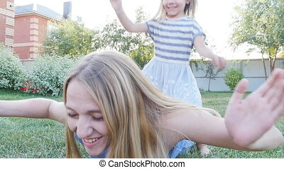 happy little girl and her mother having fun outdoors on the green grass